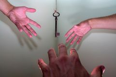People hands reaching for vintage key hanging on a string. Business success freedom concept concept for aspirations, achievement. And incentive royalty free stock photography