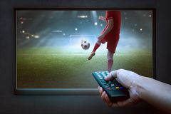 People hands with remote watching football game. On the tv Royalty Free Stock Photo