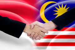 People handshake with indonesian and malaysian flags Stock Image