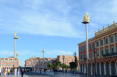 People hang around Place Massena in Nice Cote d'Azur, France. Glowing statue lamps on ground. Royalty Free Stock Photo