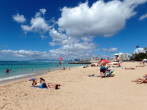 People hang out and relax on Kaimana beach with lifeguard shack Royalty Free Stock Photography