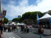 People hangout and walk around on street at North Beach Festival Stock Images