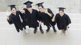 People are happy in graduation gowns and cap stand in the line. The people are happy in graduation gowns and cap stand in the line top aerial view Royalty Free Stock Images