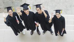 People are happy in graduation gowns and cap stand in the line. The people are happy in graduation gowns and cap stand in the line top aerial view Stock Photos