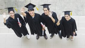 People are happy in graduation gowns and cap stand in the line. The people are happy in graduation gowns and cap stand in the line top aerial view Stock Photography