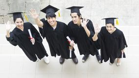 People are happy in graduation gowns and cap stand in the line. The people are happy in graduation gowns and cap stand in the line top aerial view Royalty Free Stock Photography