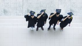 People are happy in graduation gowns and cap stand in the line. The people are happy in graduation gowns and cap stand in the line top aerial view Stock Photo