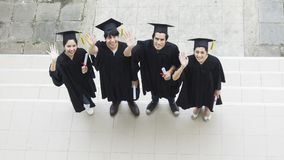 People are happy in graduation gowns and cap stand in the line. The people are happy in graduation gowns and cap stand in the line top aerial view Royalty Free Stock Photos