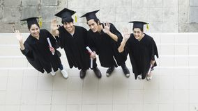 People are happy in graduation gowns and cap stand in the line. Top aerial view Royalty Free Stock Image