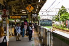 People at Harajuku JR station, Tokyo. TOKYO, JAPAN - MAY 7, 2017:  Unidentiified passenger people at Harajuku platform while arrived JR train almost stop to Stock Images