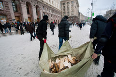 People harvest wood for fires on the frosty winter street in front of the city administration during anti-government protest Royalty Free Stock Photos