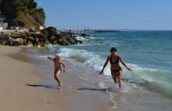 People have fun. Happy mother and son have fun at sea beach running away from the waves stock images