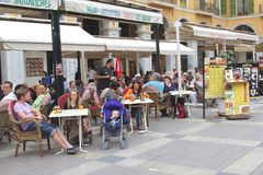 People chill at a trendy terrace in Palma, isle of Mallorca,Spain. People have fun and enjoy at an outdoor terrace at the Plaza Mayor in the capital Palma de Stock Photo