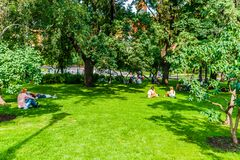 People have rest on the green grass of the Alexander garden Stock Photos