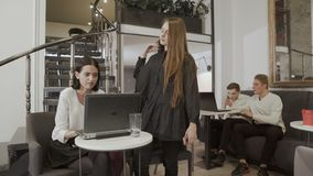 People have working process in the hall. Young attractive workers sit in the co-working space at the table. Two women discuss their work at laptop. Other two stock video footage