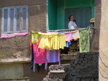 House wife Woman at balcony drying clean cloth in the sun. Housewife veiled Arabic Woman in galabya at balcony drying clean cotton cloth in the sun Stock Photo