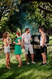 People having a barbecue grill party with drinks, food and cooking outdoor. Camping concept with friends and people. Young people having a barbecue grill party royalty free stock images