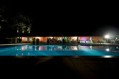 People having dinner near swimming pool. Dinner at night near swimming pool with high contrast Stock Images