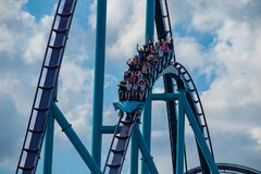 People having fun amazing Mako rollercoaster on lightblue cloudy sky background at  Seaworld 2. Orlando, Florida. April 26, 2019. People having fun amazing Mako royalty free stock image
