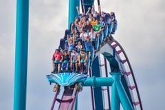 People having fun Mako Rollercoaster on lightblue cloudy sky bakcground at Seaworld 8