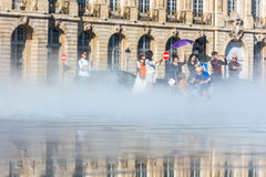 People having fun in a mirror fountain in Bordeaux, France Royalty Free Stock Photo