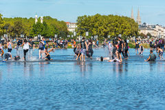 People having fun in a mirror fountain in Bordeaux, France Stock Image
