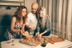 People having fun at a party with martini and pizza Royalty Free Stock Photos