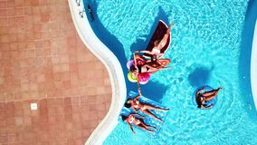 People having fun in summer at the pool with trendy coloured inflatable mattress lilos - couple of beautiful girls lay down and en