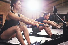 People having hard workout on rowing machines