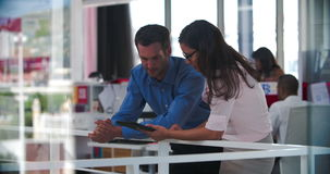 People Having Informal Meeting In Modern Open Plan Office. Businessman and businesswoman leaning against balcony railing having informal in modern open plan stock footage