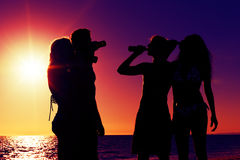 People having party at beach with drinks. People (two couples) on the beach having a party, drinking and having a lot of fun in the sunset (only silhouette of Stock Images