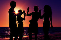 People having party at beach with drinks. People (two couples) on the beach having a party, drinking and having a lot of fun in the sunset (only silhouette of Royalty Free Stock Photo