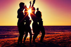 People having party at beach with drinks. People (two couples) on the beach having a party, drinking and having a lot of fun in the sunset (only silhouette of Royalty Free Stock Image