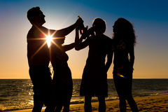 People having party at beach with drinks. People (two couples) on the beach having a party, drinking and having a lot of fun in the sunset (only silhouette of Stock Photography