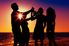 People having party at beach with drinks. People (two couples) on the beach having a party, drinking and having a lot of fun in the sunset (only silhouette of Royalty Free Stock Photography