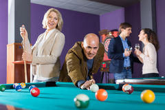People having pool game. Positive middle class people having pool game and laughing in billiard club Royalty Free Stock Photo