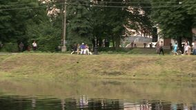 People having rest by the lake in a city park view. People having rest by the lake in a summer city park view stock video