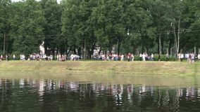 People having rest by the lake in a city park view. People having rest by the lake in a summer city park view stock video footage
