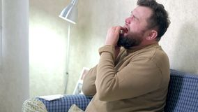 People, healthcare, dentistry and problem concept - unhappy bearded man suffering toothache at home. stock footage