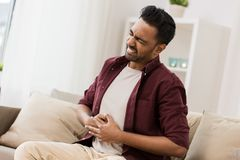 Unhappy man suffering from stomach ache at home. People, healthcare and problem concept - unhappy man suffering from stomach ache at home Stock Image