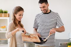 Couple cooking food at home kitchen. People and healthy eating concept - couple cooking food at home kitchen Stock Image