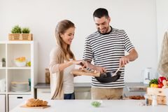 Couple cooking food at home kitchen Stock Images