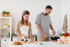 Couple cooking food at home kitchen. People and healthy eating concept - couple cooking food at home kitchen stock images
