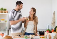 Couple cooking food and drinking wine at home Stock Photos