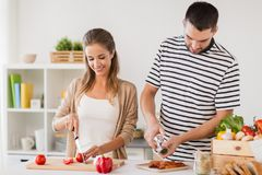 Happy couple cooking food at home kitchen Royalty Free Stock Images