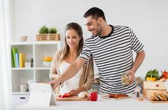 Happy couple with tablet pc cooking food at home Royalty Free Stock Photo