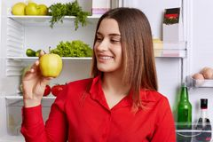 People and healthy nutrition concept. Adorable young woman with cheerful expression, holds green fresh apple, demonstrates her bre stock photography
