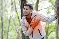 People with a heart attack. Asian cardiac arrest running young man heart attack in park.Severe heartache Stock Images