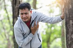 People with a heart attack. Asian cardiac arrest running young man heart attack in park.Severe heartache Stock Photos
