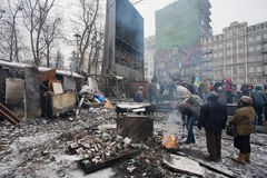 People heating by the fire near the barricades after fights with police on the broken street of Kiev during anti-government riot Stock Photo